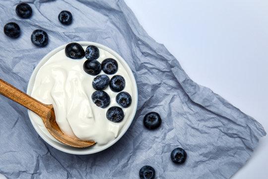 Bowl with tasty yogurt and blueberry on light background