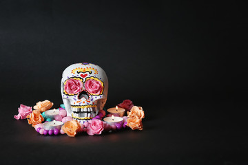Painted human skull with flowers and candles for Mexico's Day of the Dead on dark background