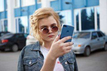 Beautiful young stylishly dressed girl walking around the city, taking a selfie on a mobile phone
