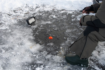Fishing on a frozen lake in winter with sonar