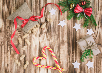 Christmas composition with a bag of peanuts with red ribbon, white stars, fir branches with a red ribbon bow, gift box and Christmas sticks in the shape of a heart on wooden background.