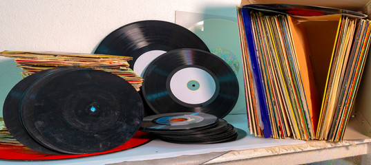45 and 33 rpm vinyl discs stack on white background