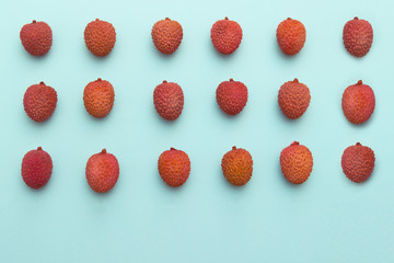 lychee fruits lie in rows on a turquoise blue background