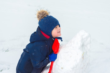 kid makes a snowman with a shovel and plays in the snow