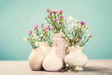 Assorted white and pink flowers in various vases on light background. Greeting card concept with copy space. Retro style toned photo.