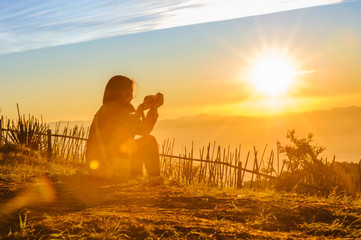 silhouette of female traveler taking photo of beautiful sunrise and mountains with blue sky  in the morning, chiang mai in thailand