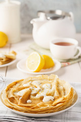 Homemade lemon crepes with custard sauce and tea.