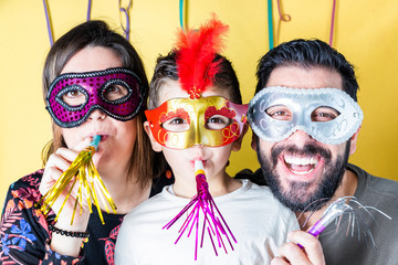 Happy family in Carnival with masks with yellow background