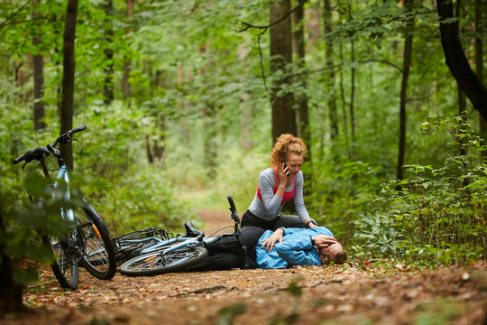 Young woman calling ambulance in the forest while leaning over her boyfriend lying on path with his leg broken