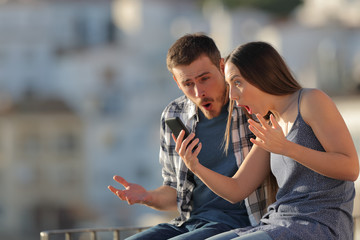 Amazed couple checking smart phone in a town