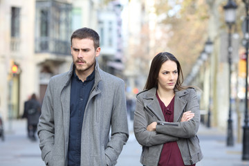 Angry couple walking in the street after argument