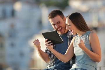 Excited couple checking tablet online content in a town