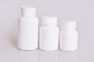 White blank medical plastic bottles of different sizes on a white background. Studio lights