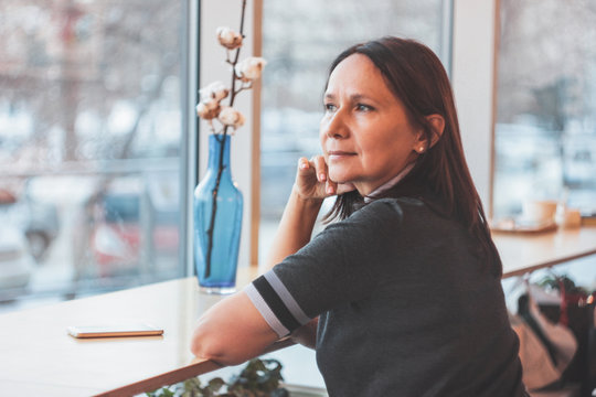 Beautiful middle-aged adult woman looking at window in cafe