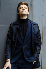 portrait of an attractive man, guy, businessman, wearing a blue suit, A coat. Hands in pockets, worth on the street.thoughtfully leaned against the wall. watches on the arm