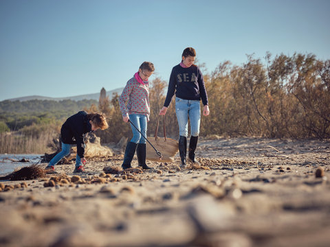 Children with litter pickers and basket picking up garbage from river shore