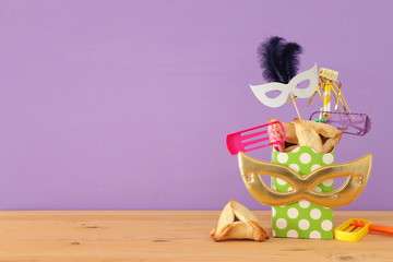 Purim celebration concept (jewish carnival holiday) over wooden table and purple background.