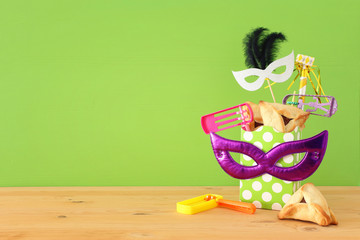Purim celebration concept (jewish carnival holiday) over wooden table and green background.