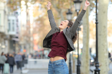Excited woman jumping in the street