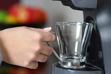 Woman hand holding an empty cup in a coffee maker