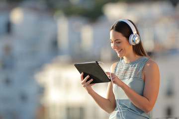 Woman litening to music browsing a tablet