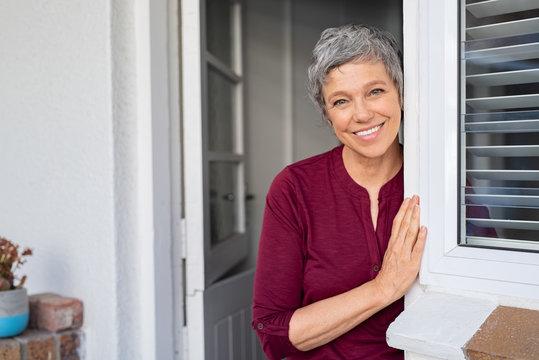 Happy senior woman leaning at door