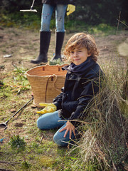 Boy with heap of garbage in hands near basket