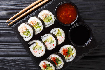 Futomaki rolls with various fillings are served with sauces close-up on a slate board. horizontal top view