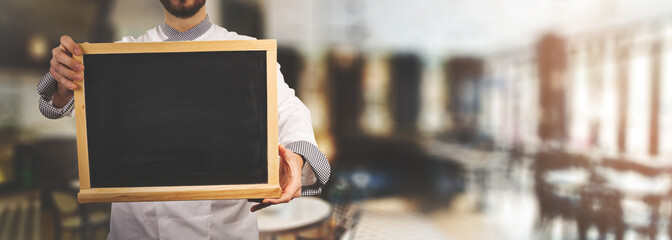 chef with blank blackboard standing in restaurant. banner copy space