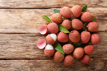 Ripe lychee fruits with green leaves close-up on wooden. Horizontal top view