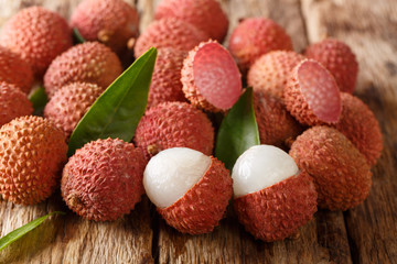 Fresh lychee and peeled showing the red skin and white flesh with green leaf. horizontal