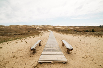 Stairs to the beach. A wooden staircase leads to a wide sandy beach on the picturesque shore on a beautiful and windy summer day.