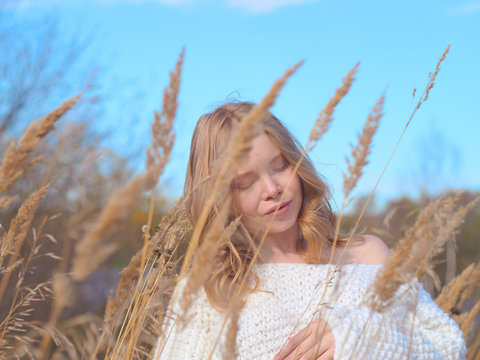 Beautiful pregnant woman in a white woolen sweater. Beautiful pregnant woman in high dry grass against the blue sky.