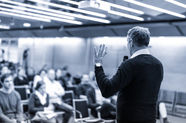 Expert giving a talk on business conference workshop. Unrecognizable people in audience at the conference hall. Business and entrepreneurship event. Black and white, blue toned.