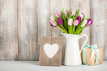 Fresh colorful tulips in a jug, gift box and heart shaped frame on table