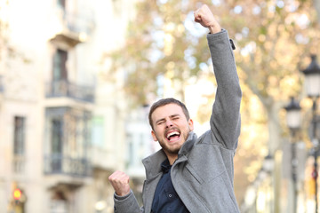 Excited man raising arm in the street