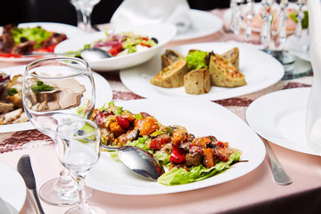 Fresh salad with tomatoes and meat. Delicious prepared and decorated food on table in restaurant. Restaurant table setting decor with glasses. Catering table