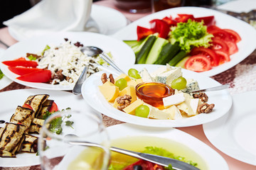 A plate with a set of different cheeses: Mazda, Parmesan, Blue Cheese, served with fruits. Cheese sliced. Snack to wine. Delicious prepared and decorated food on table in restaurant. Restaurant table