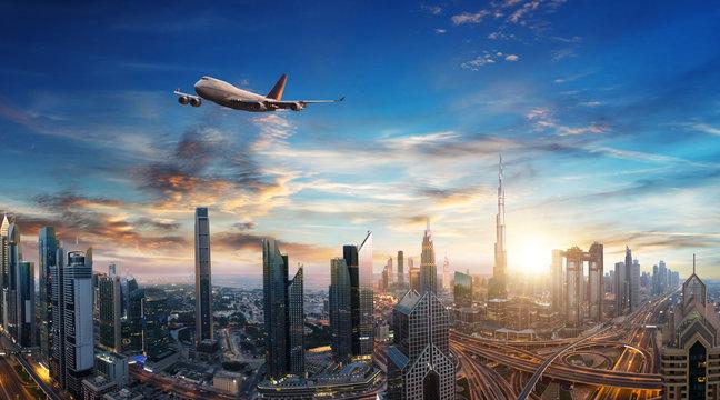 Commercial jet plane flying above Dubai city