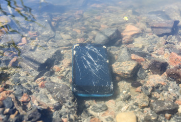 Black broken crashed smartphone is lying in the water. Phone in the lake outdoors.