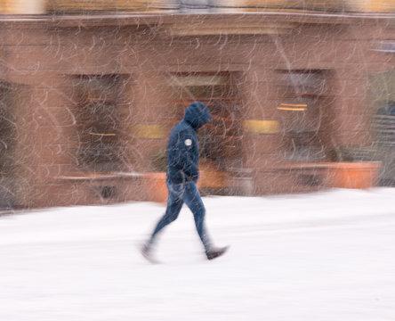 Woman walking down the street in winter snowy day in motion blur