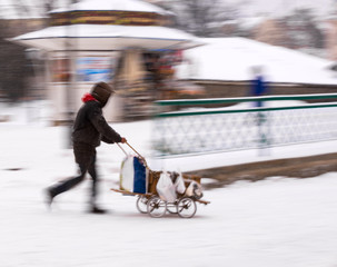 Poor man pulling a cart with cardboard in the city in snowy winter day