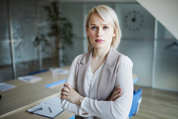 Young serious and concentrated blonde businesswoman with her arms crossed on chest looking at you