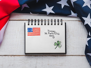 St.Patrick's Day. Beautiful card. Notepad with congratulatory inscription. Isolated background, close-up, top view, wooden surface. Congratulations for loved ones, relatives, friends and colleagues