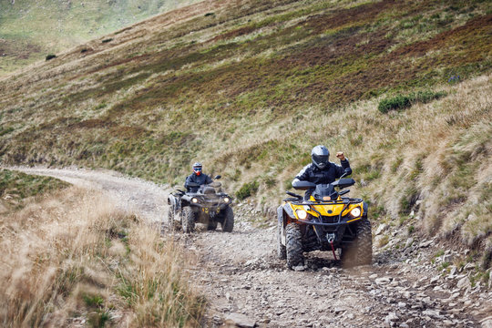 Front view of quad bikes zipping along a country road.