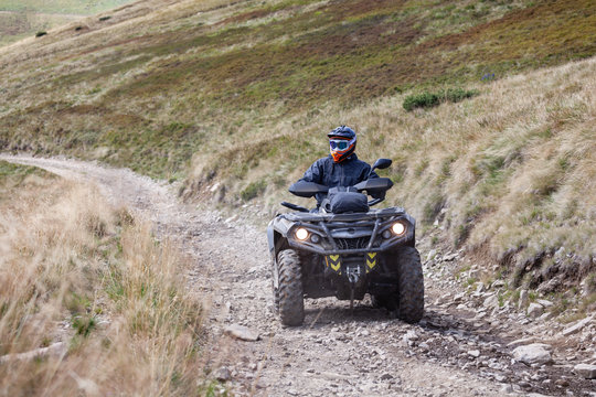 Front view of quad bike zipping along a country road.