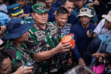 Indonesia's Navy Commander Rear Admiral Yudo Margono holds the cockpit voice recorder (CVR) of a Lion Air JT610 that crashed into Tanjung Karawang sea, on the deck of Indonesia's Navy ship KRI Spica-934 at Karawang sea in West Java