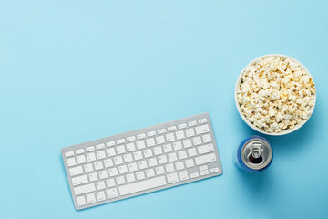 Keyboard and tin can with a drink, energy drink, a bowl of popcorn on a blue background. The concept of watching movies, TV shows, sports events online. Flat lay, top view