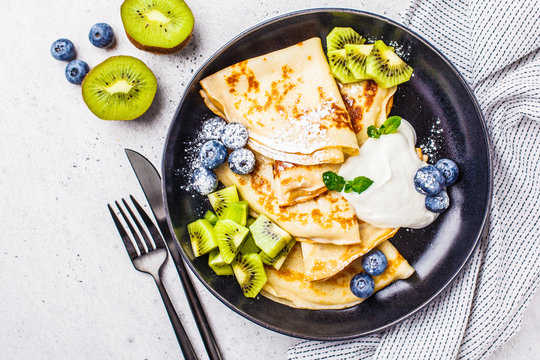 Thin crepes with curd cream, kiwi and blueberries in a black plate, top view.
