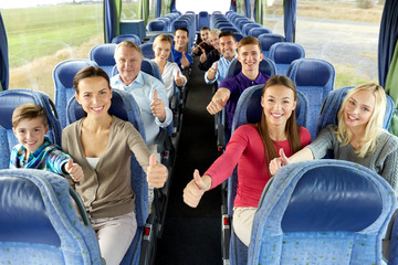 transport, tourism and travel concept - group of happy passengers travelling by bus and showing thumbs up